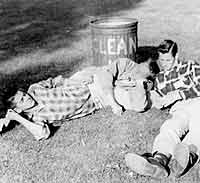 "Thumbnail: Ronnie Busch, Charlie Babbitt, Richard Gatley lying next to a ""Clean Up"" trash can"
