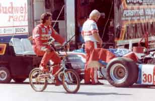 Thumbnail: Mario Andretti biking in the garage area, just prior to signing my t-shirt  CLICK to see a larger version